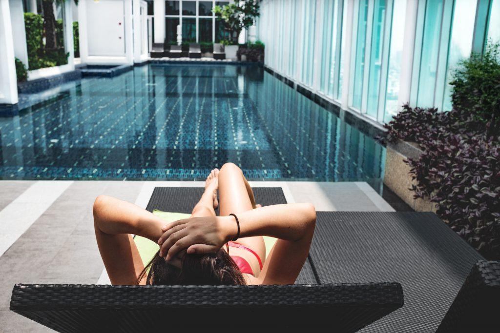 Femme qui bronze sur un transat, au bord d'une piscine