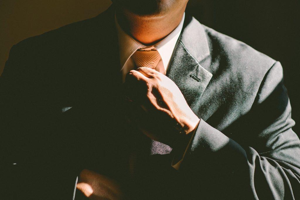 vue sur le torse d'un homme en costume qui ajuste sa cravate