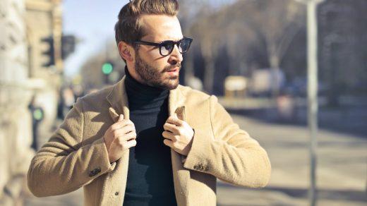 homme à lunettes portant un pull noir et une veste beige